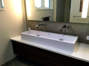 A newly remodeled bathroom with a white trough-style sink
